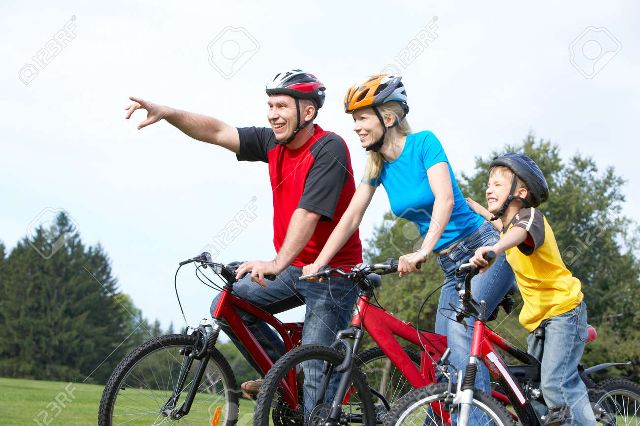 Happy family. Father, mother and son riding  in the park Stock Photo - 5594070