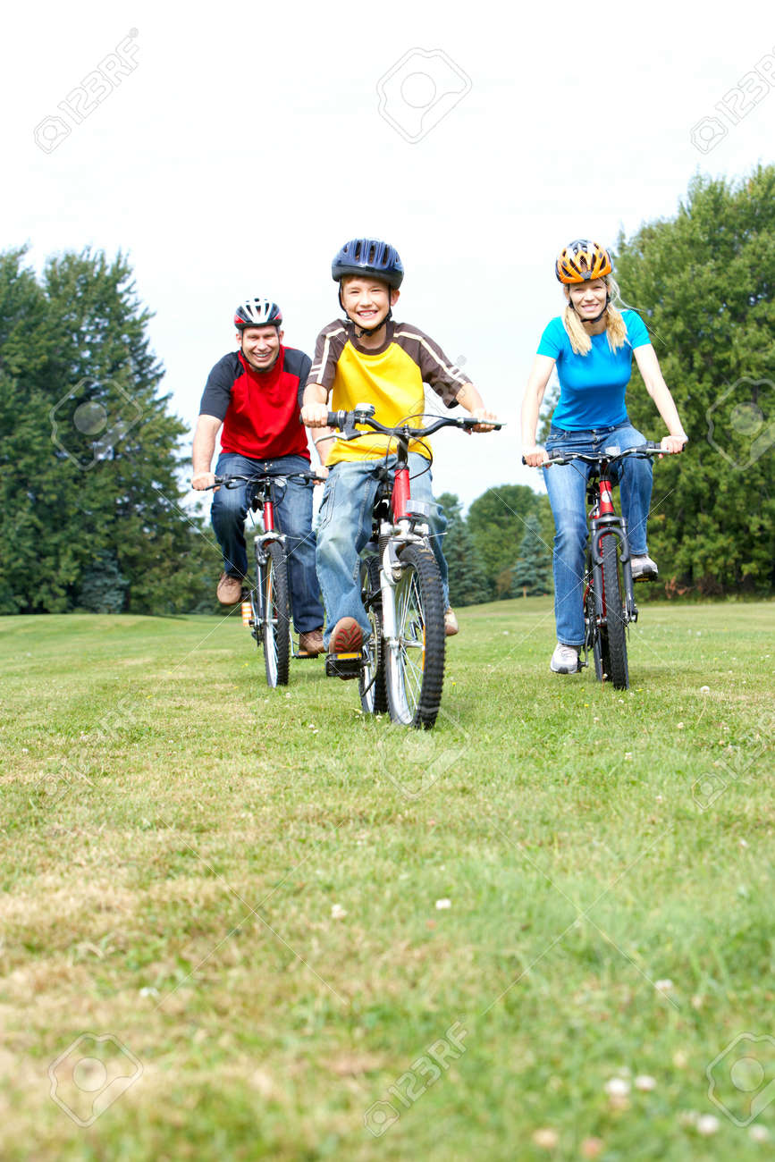 Happy family. Father, mother and son riding  in the park Stock Photo - 6111515