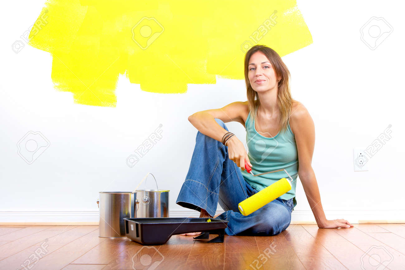 Person painting wall - Smiling Beautiful Woman Painting Interior Wall Of Home Renovation Stock Photo 6744365