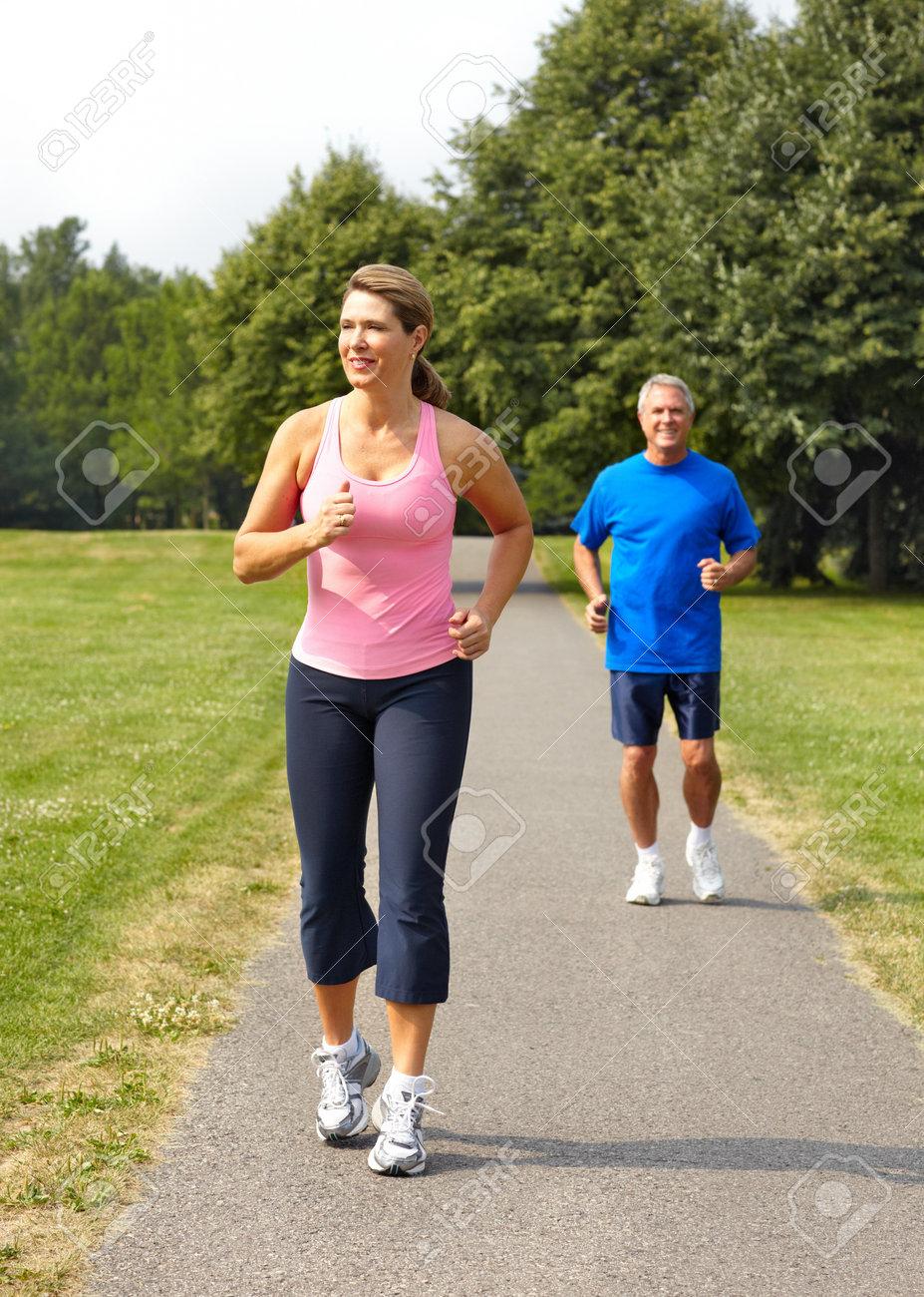 Happy elderly seniors couple jogging in park Stock Photo - 7362922