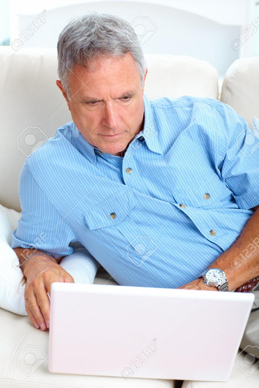 Smiling elderly senior man with laptop at home Stock Photo - 7362921