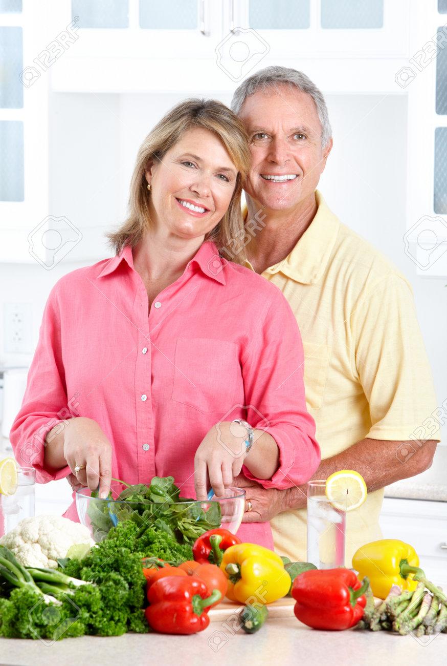 Happy seniors couple cooking at kitchen Stock Photo - 7365015
