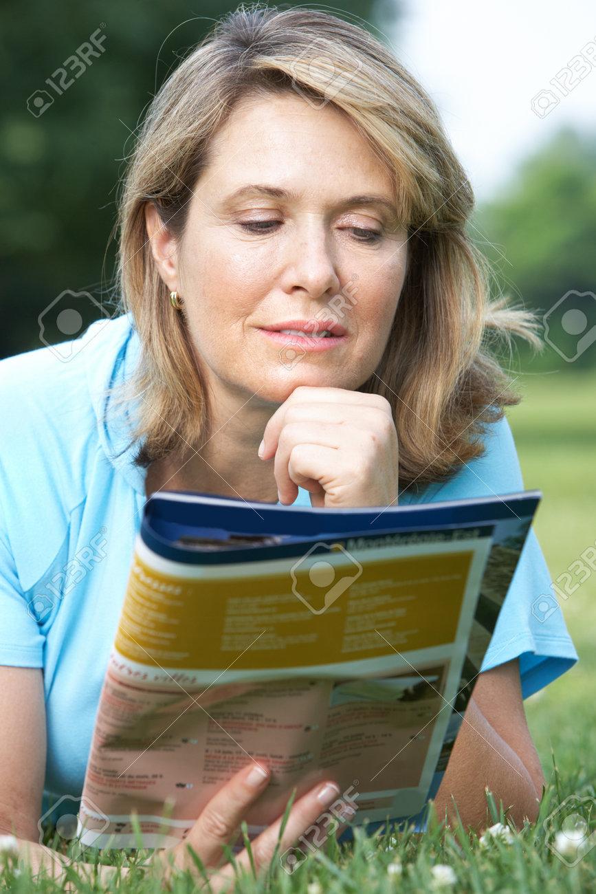 Happy smiling elderly woman reading a magazine Stock Photo - 7365002