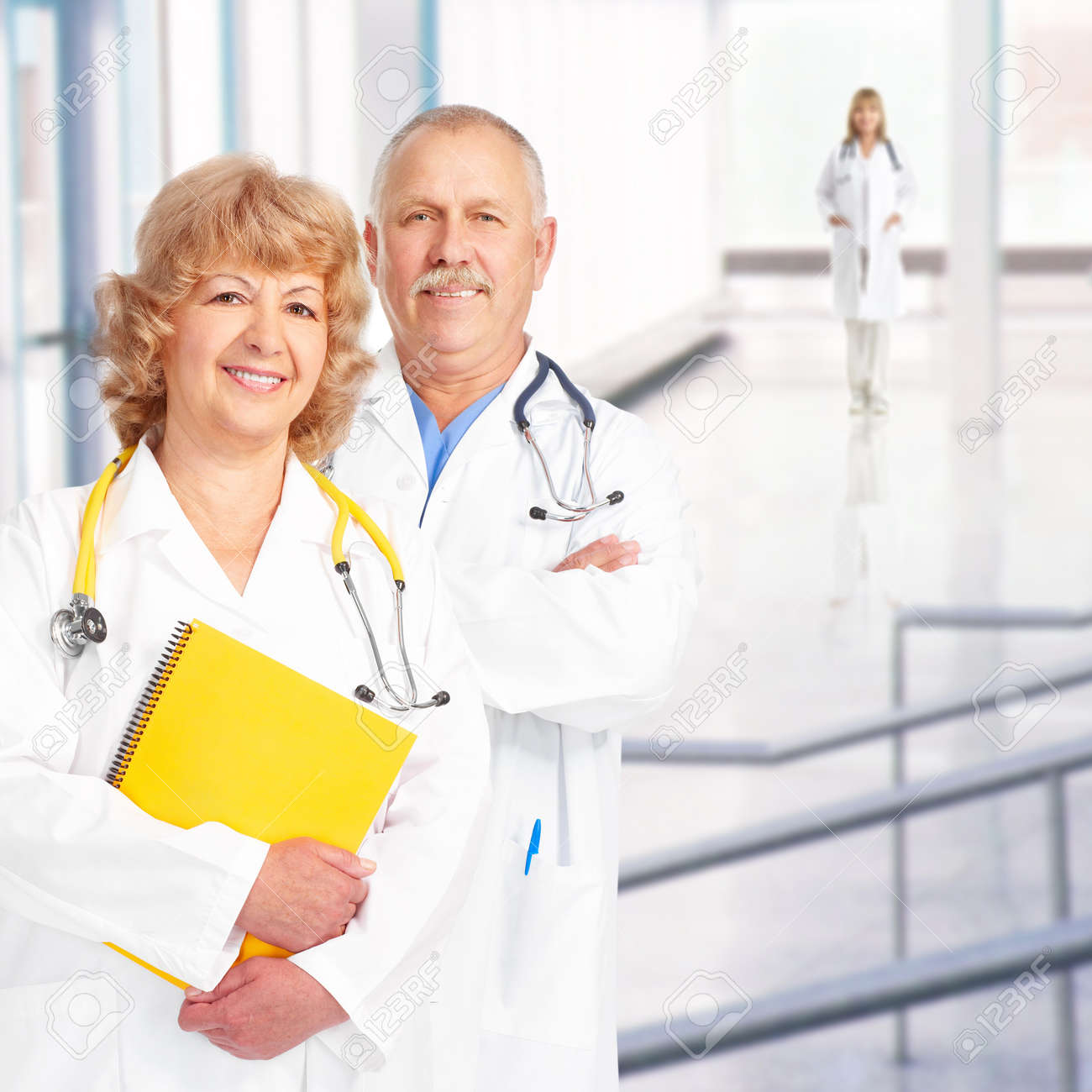 Smiling medical doctors with stethoscopes. Over blue background Stock Photo - 7702630