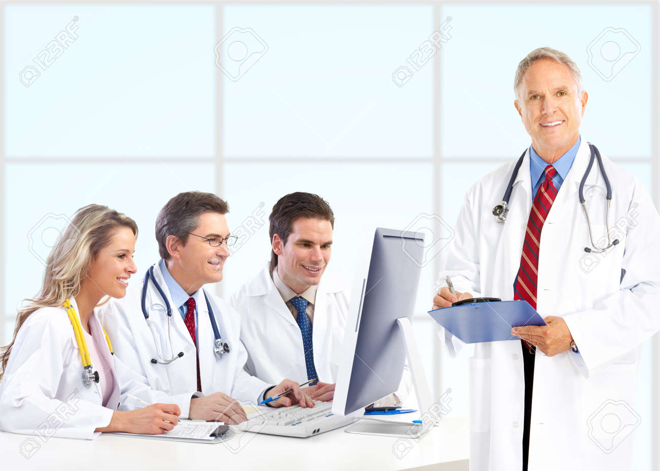 Smiling medical doctors with stethoscopes working with computer. Stock Photo - 8074324