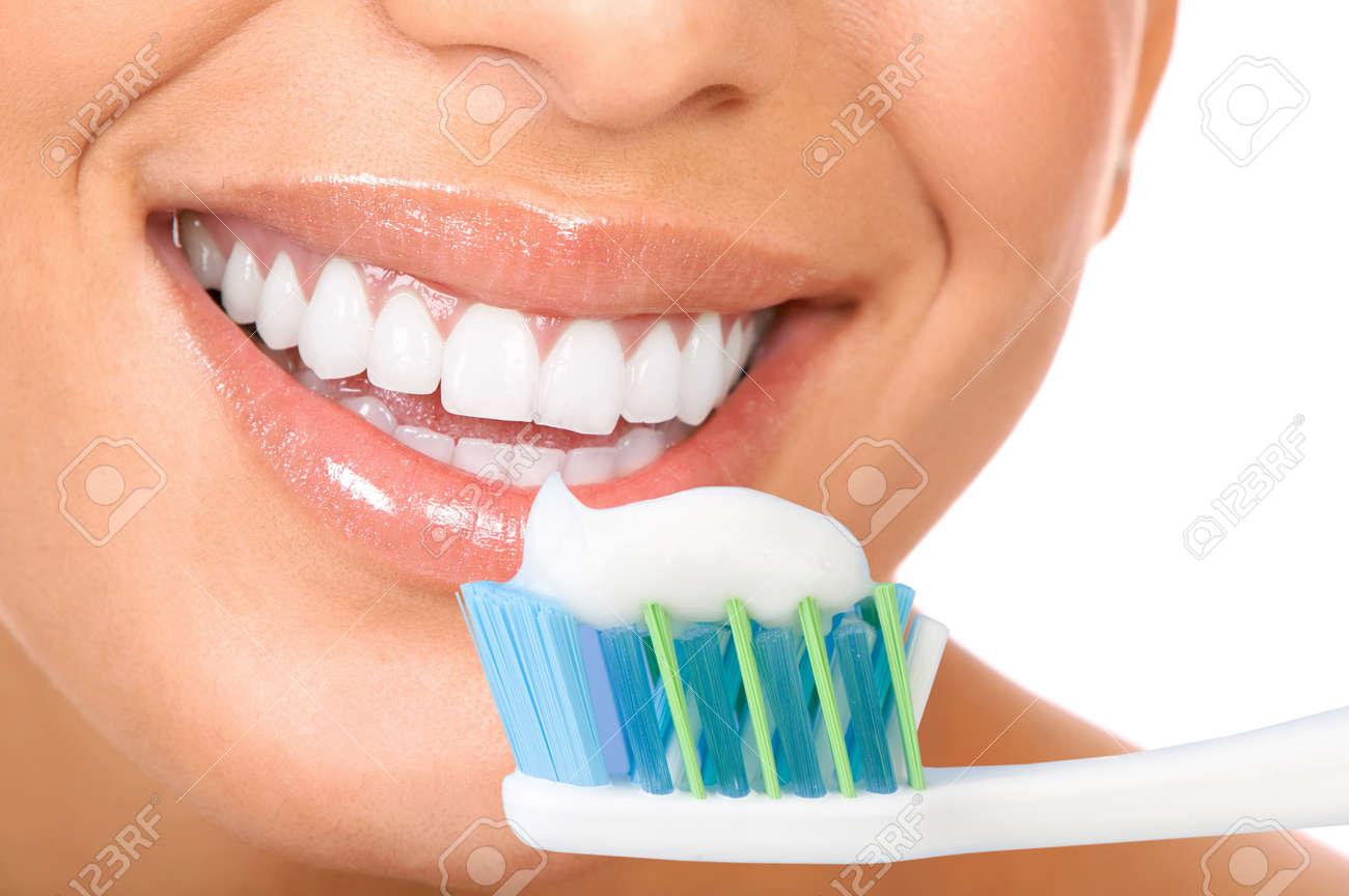 Smiling  young woman with healthy teeth holding a tooth-brush Stock Photo - 8170101