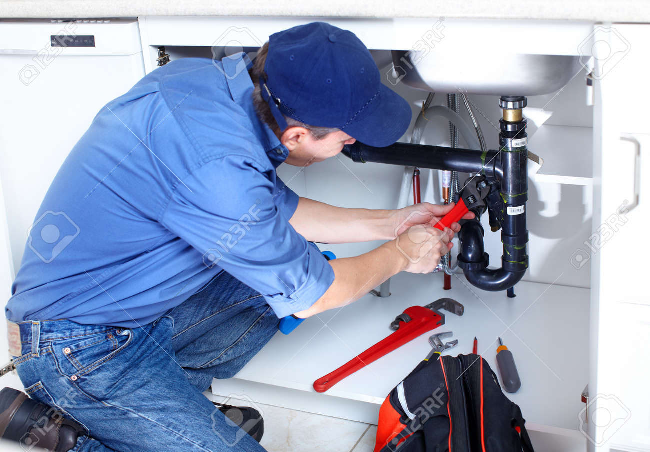 Mature plumber fixing a sink at kitchen - 8255783