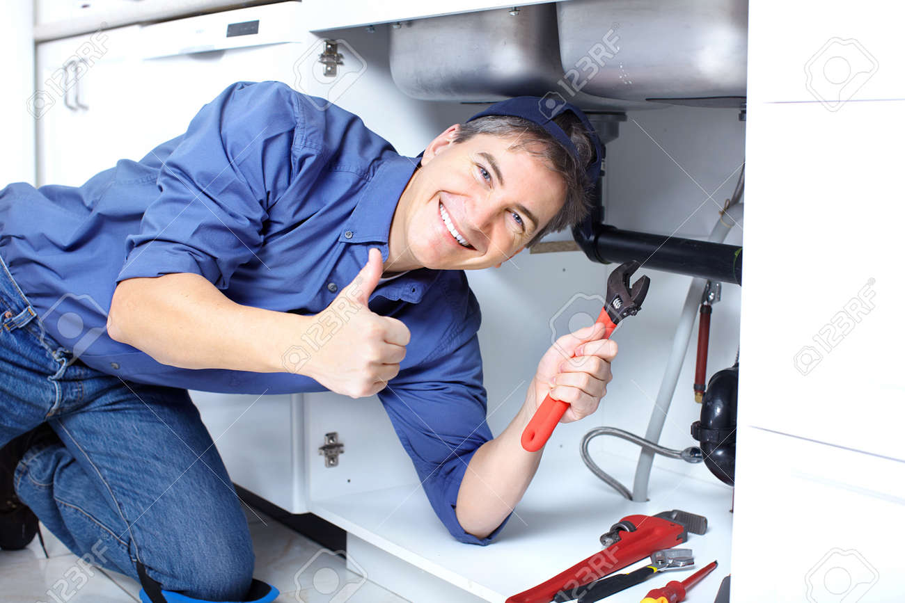 Mature Plumber Fixing A Sink At Kitchen Stock Photo, Picture And ...