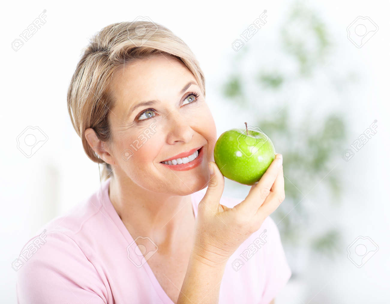 Mature smiling woman with apple Stock Photo - 8430717