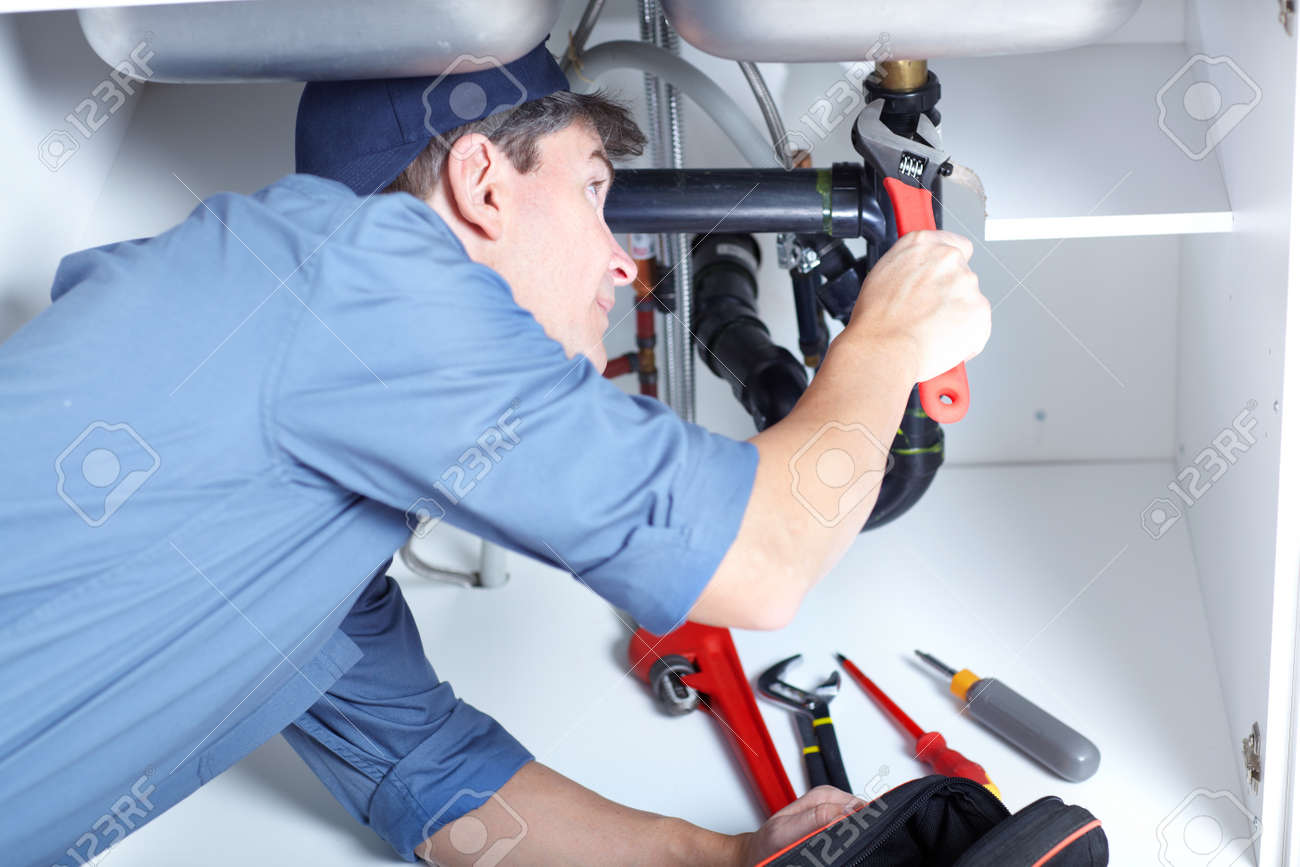 Mature plumber fixing a sink at kitchen Stock Photo - 8617055