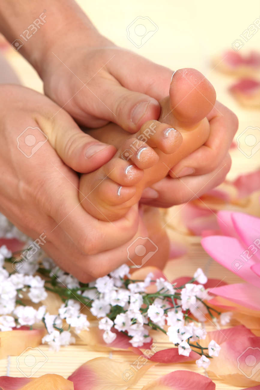 Female feet massage and flowers Stock Photo - 8863773