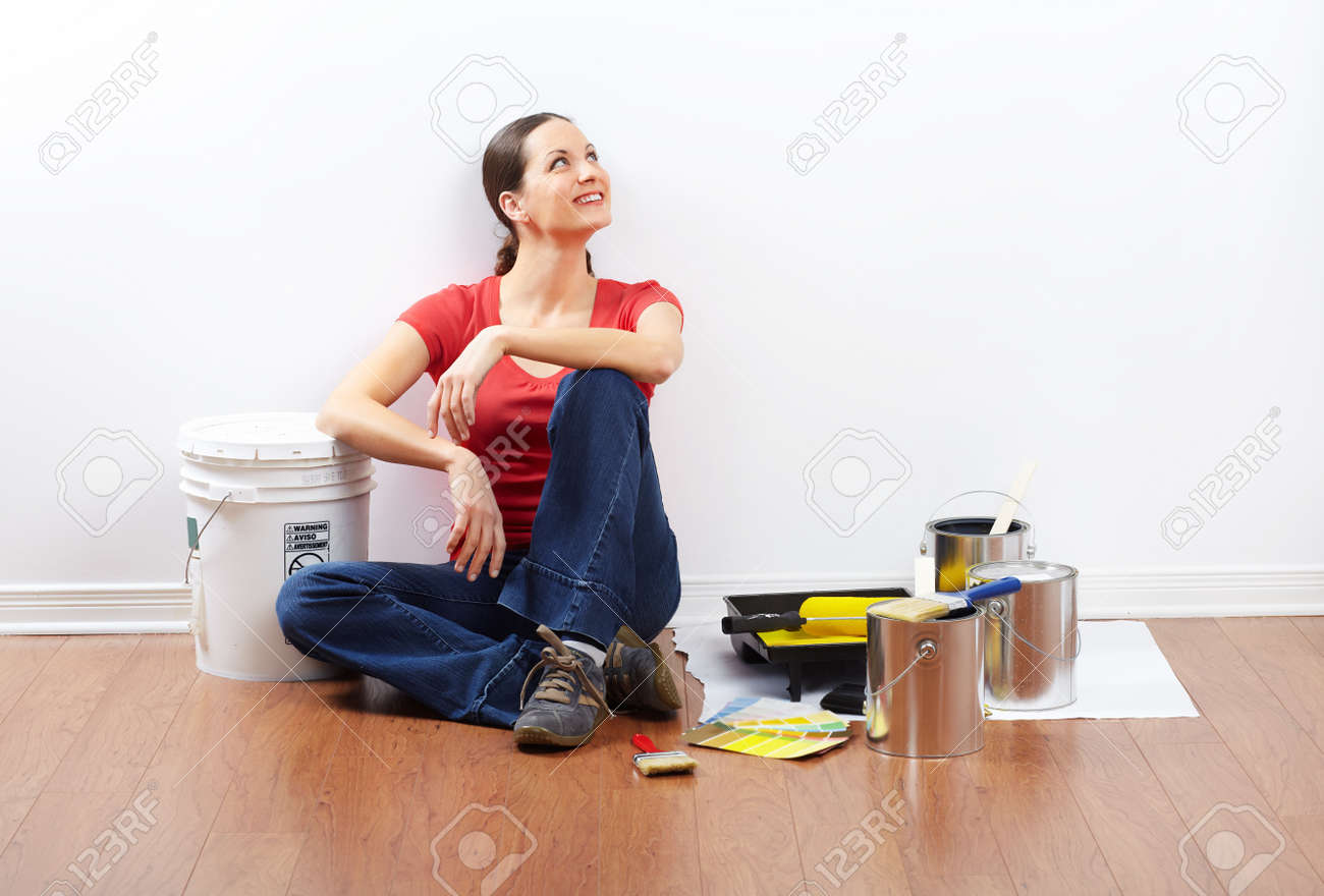 smiling beautiful woman painting interior wall of home. Stock Photo - 8863726