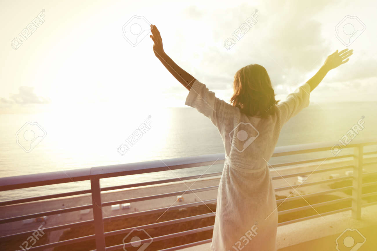 Happy woman with hands up to sky looking at ocean Stock Photo - 22219063
