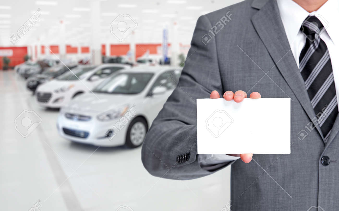 Auto Dealer With A Business Card Over Vehicles Background. Stock ...