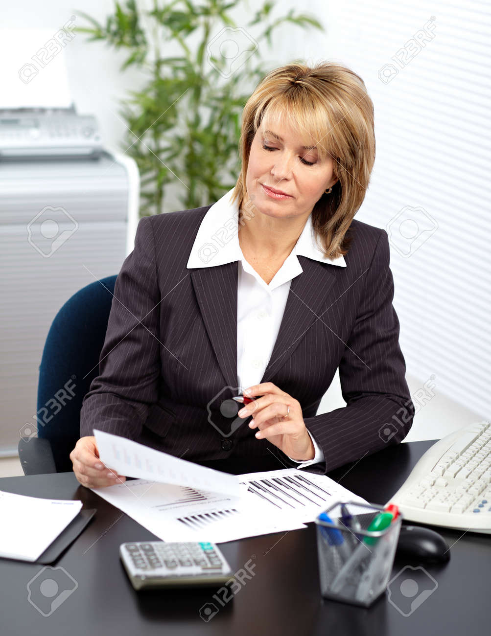 beautiful mature business woman working in modern office. stock