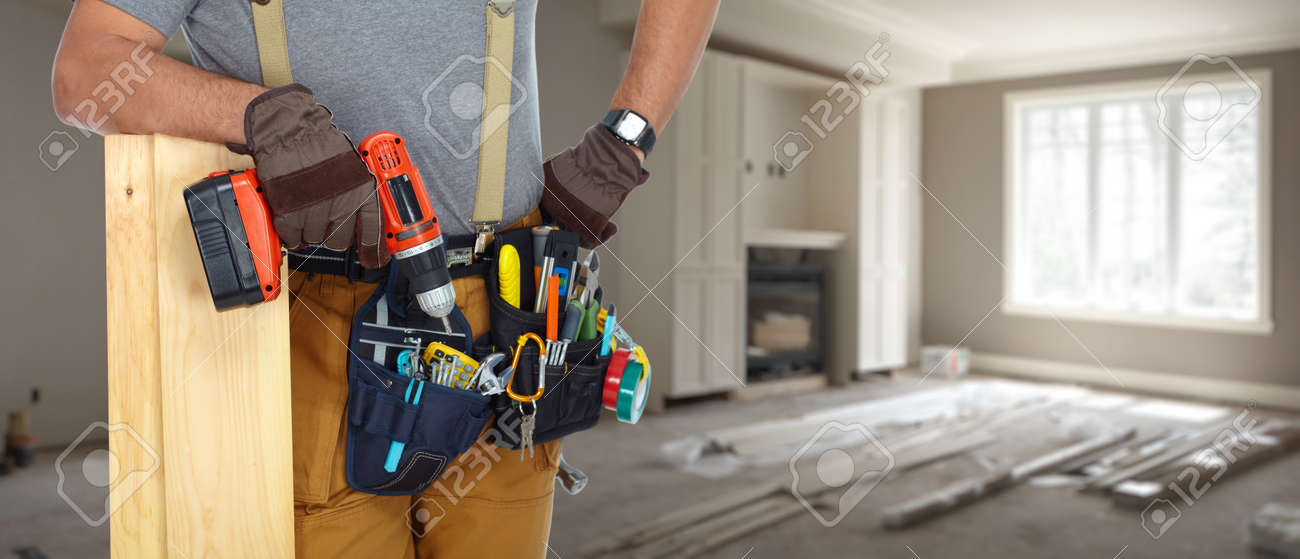 Builder handyman with construction tools on house background. - 53296158