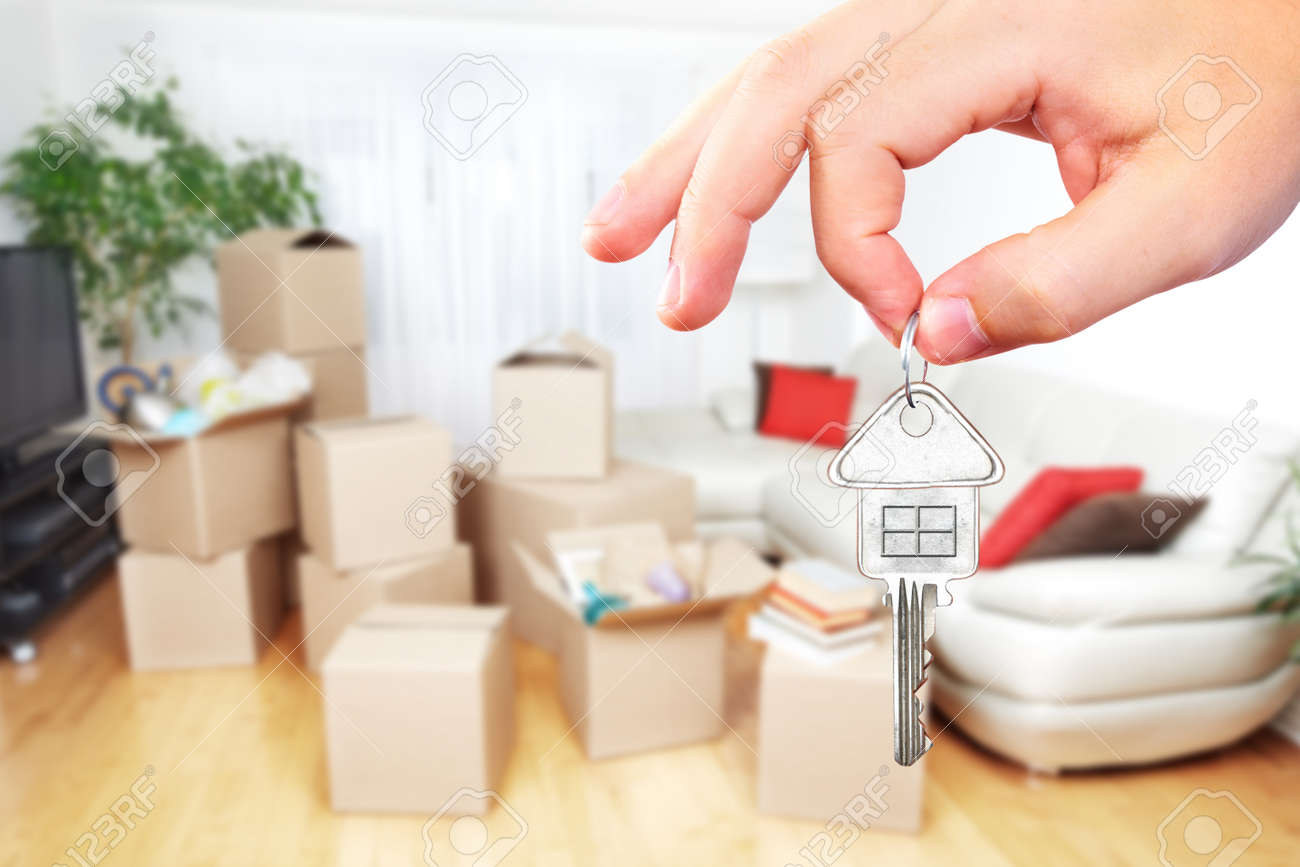 Hand with house key. Real estate and moving background. Standard-Bild - 53607811