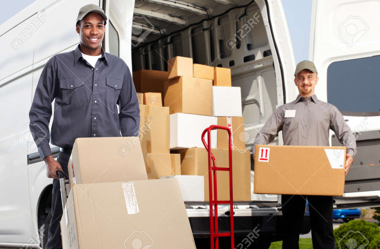 Smiling postman with a box near shipping truck. - 53978805