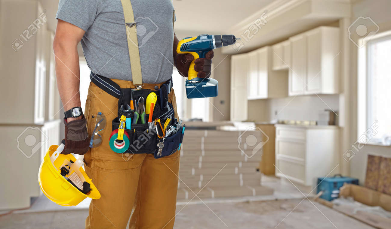 Builder handyman with construction tools on house background. Standard-Bild - 53980773