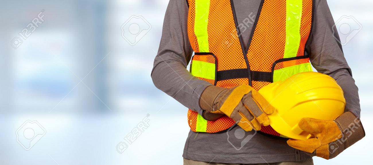 Construction worker with helmet in orange security vest. Standard-Bild - 56592817