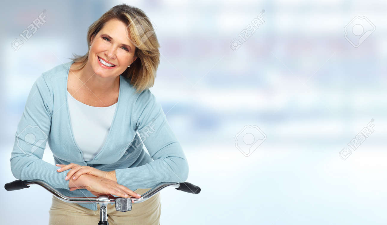 Beautiful senior woman with bicycle over blurred background. Standard-Bild - 58074349