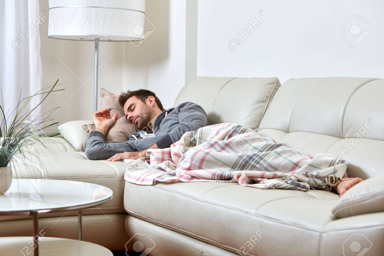 Handsome Man Sleeping Sofa At Cozy Relaxing Apartment. Stock Photo    64269318