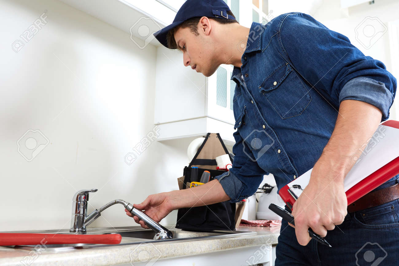 Professional plumber doing reparation in kitchen home. Standard-Bild - 64468121