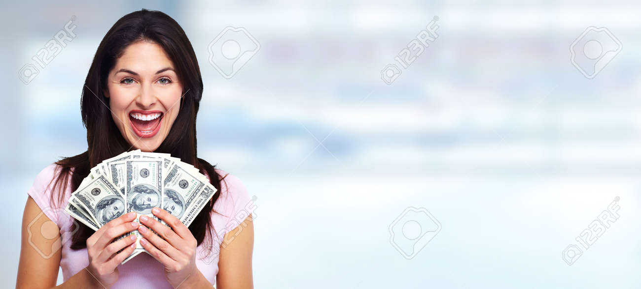 Happy young smiling woman holding cash over blue background Standard-Bild - 64890881