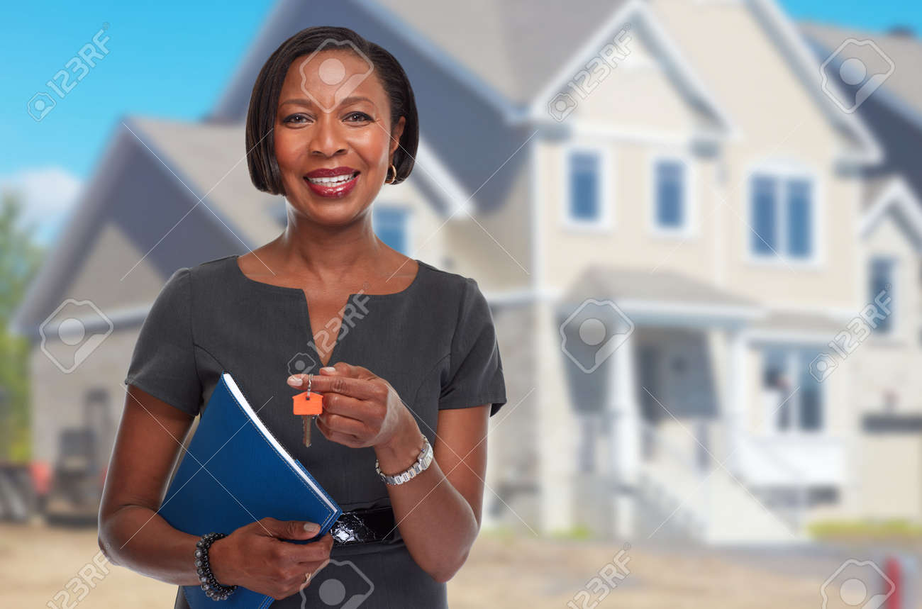 Smiling afro american real estate agent woman with house key. Standard-Bild - 64969871