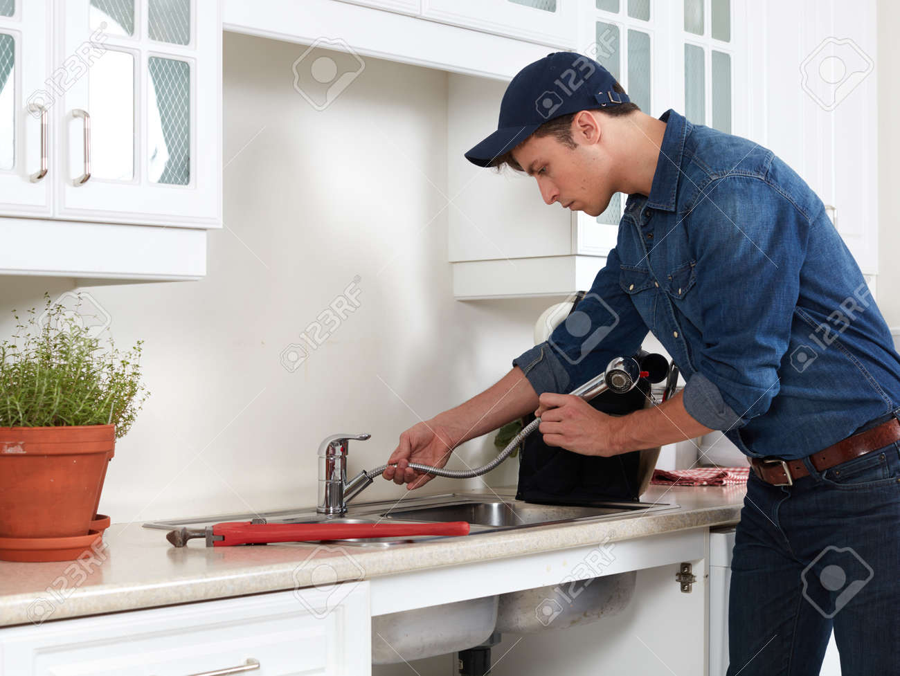 Professional Plumber Doing Reparation In Kitchen Home. Stock Photo ...