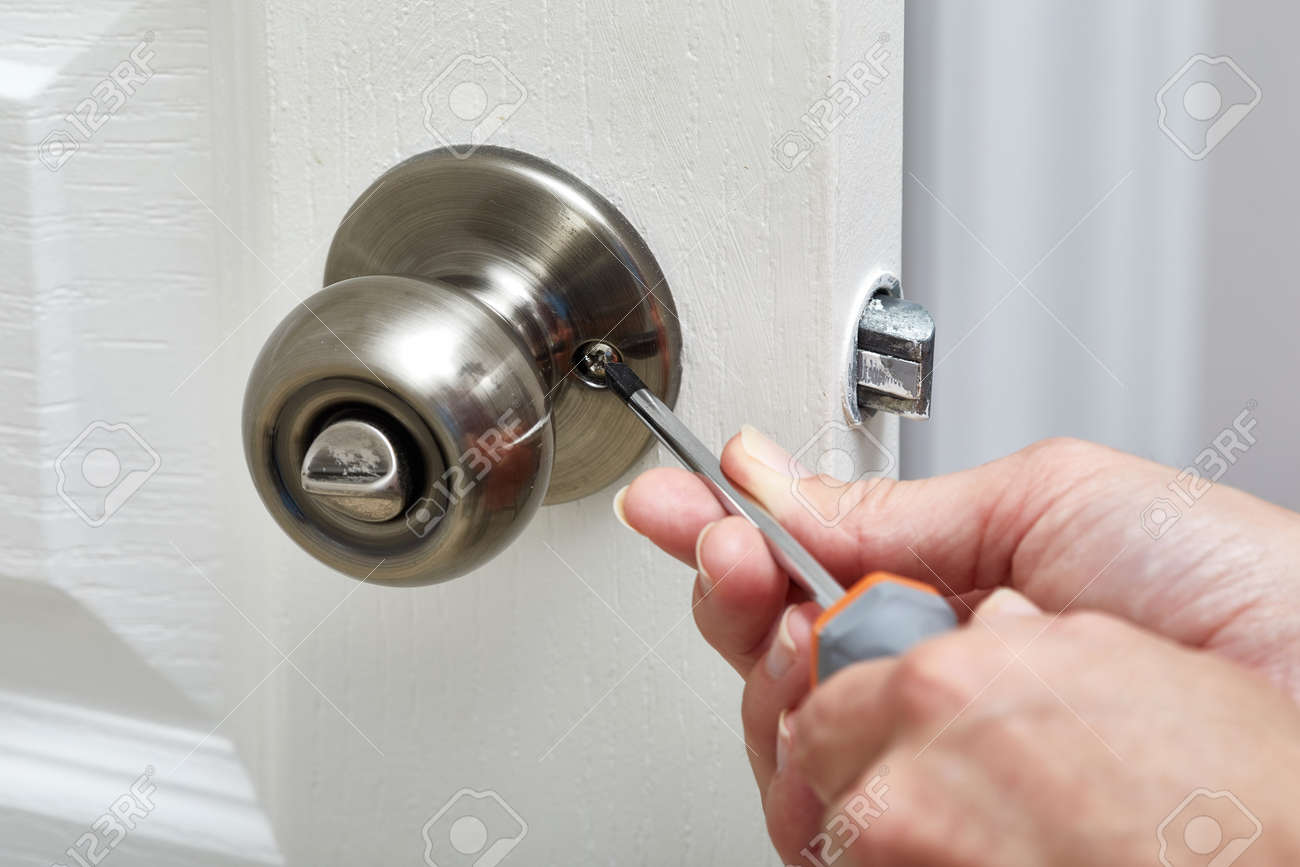 Hands with screwdriver fixing a door lock. Stock Photo - 65958866 & Hands With Screwdriver Fixing A Door Lock. Stock Photo Picture And ...