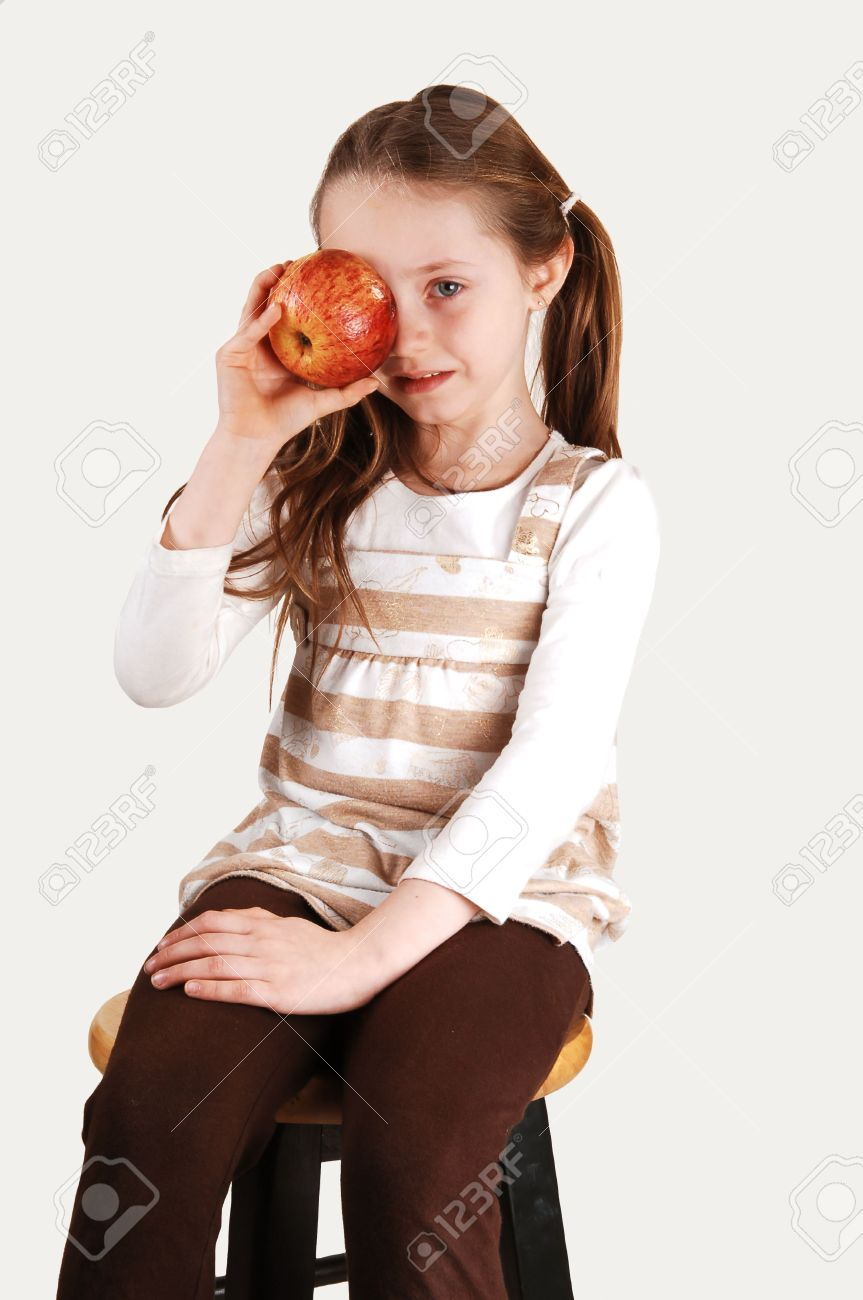 An Little Girl Sitting On A High Chair And Holding A Red Apple On Her Right