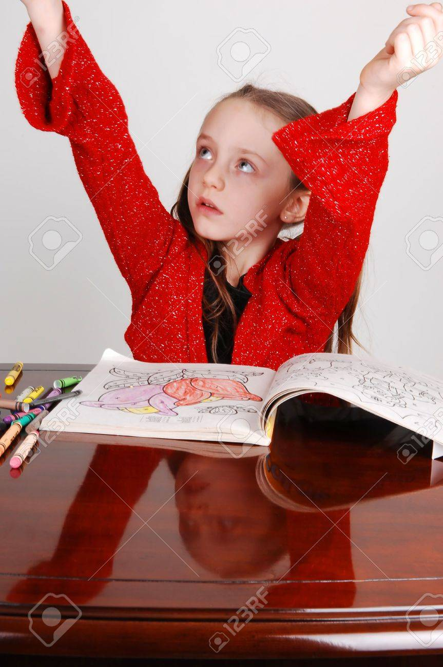 Little Girl In A Red Sweater Sitting On The Table And Coloring ...