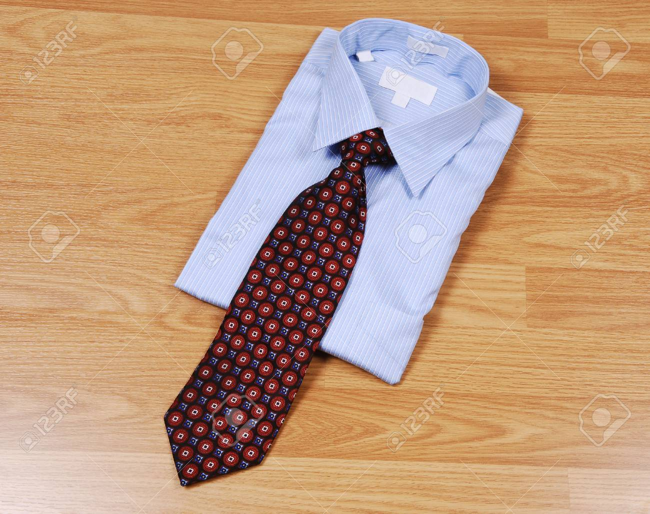 A light blue dress shirt on a wood surface with an red and black tie for sale in the store. Stock Photo - 4804283