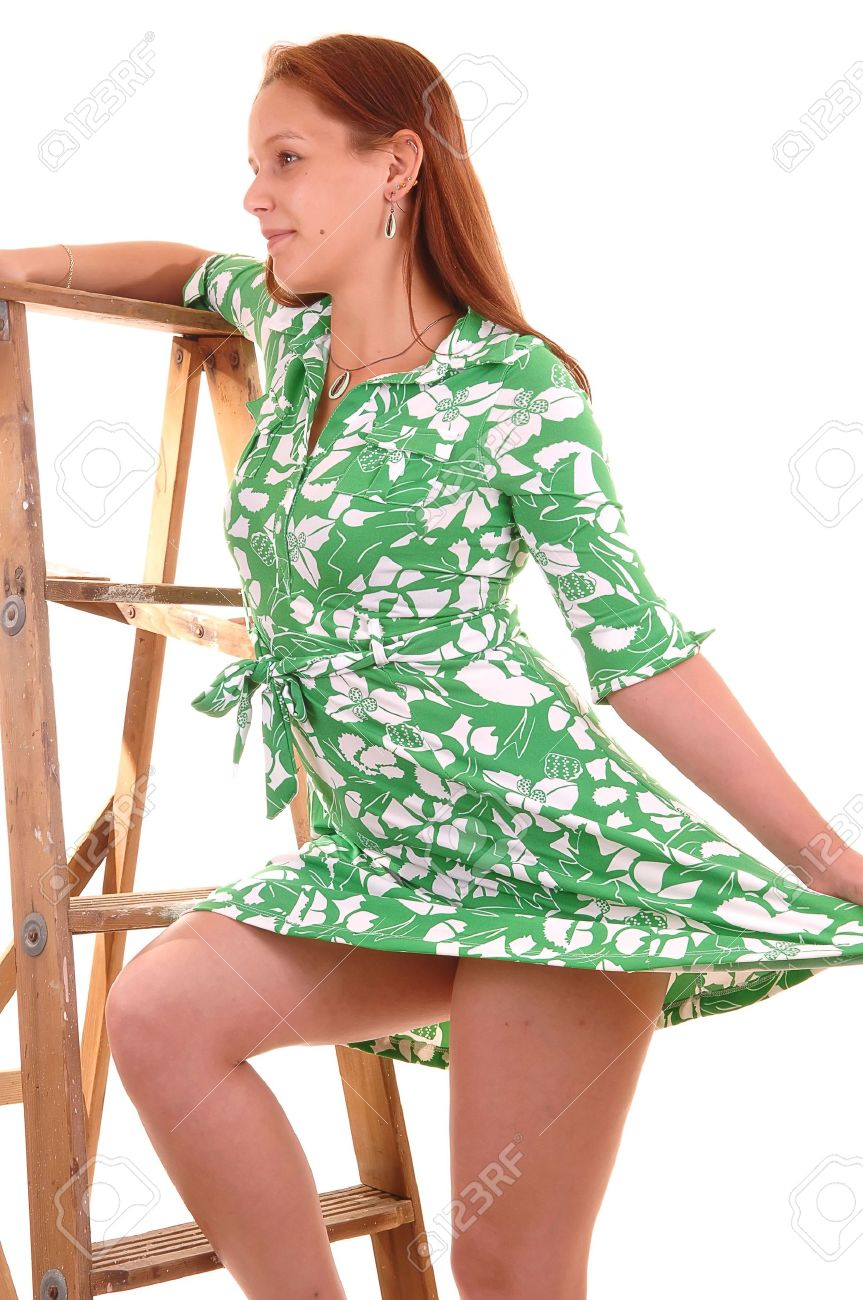 96f2ff5a6 Happy Young Woman In A Green Dress Standing On An Stepladder.. Stock ...
