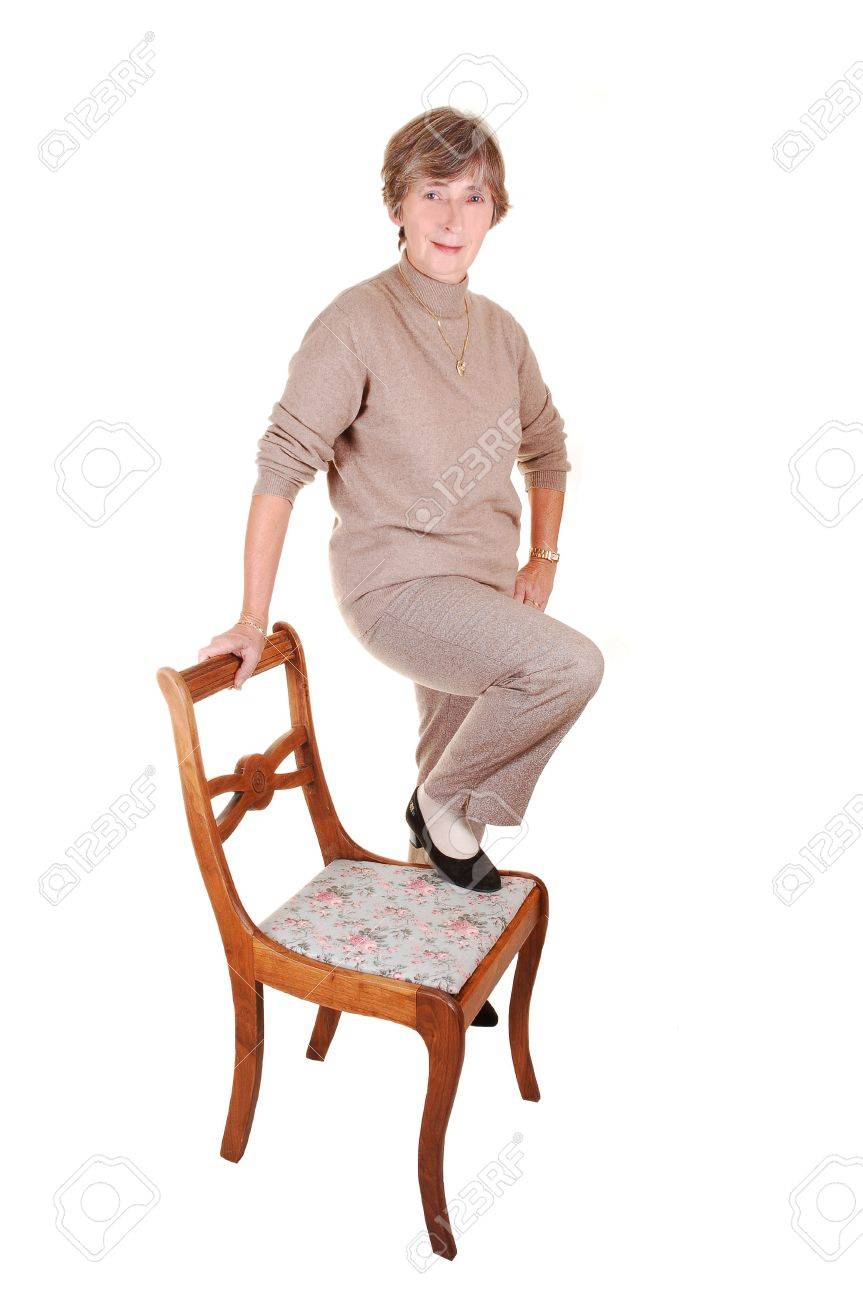 A lady in dress pants and beige sweater with high heels standing on an old chair in the studio for white background isolated. Stock Photo - 5852446