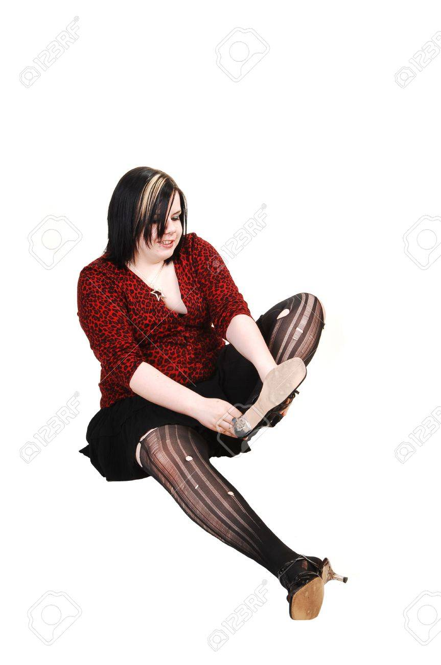 A young girl in a black short skirt and red blouse sitting on the floor and putting her high heels on in ripped up pantyhose, on white background. Stock Photo - 5908408