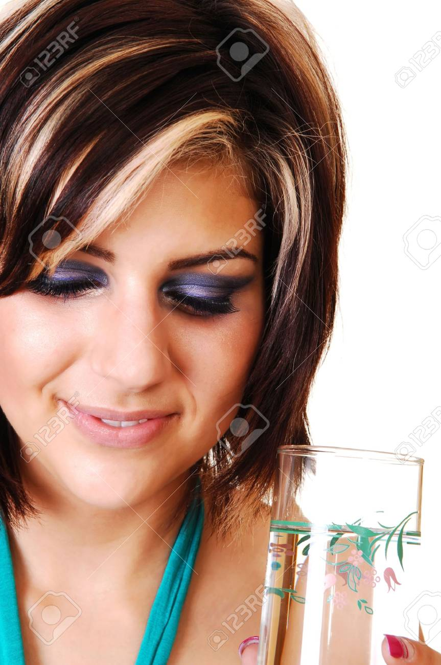 An pretty smiling girl with a glass full of water, in a closeup shot, standing in the studio and looking down, for white background. Stock Photo - 6764248