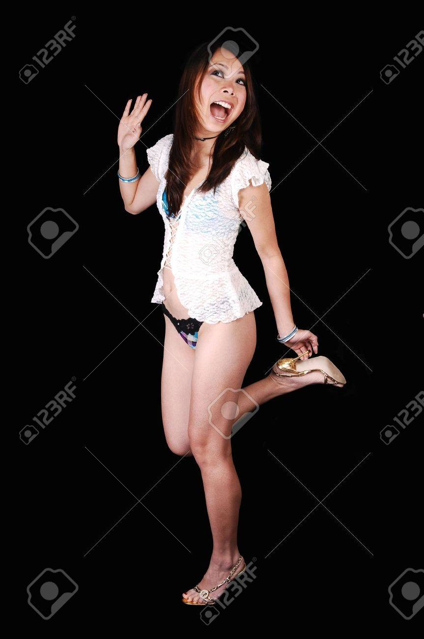 A young Chinese woman dancing in the studio in gold high heels a white blouse and lingerie thongs, laughing for black background. Stock Photo - 6820692