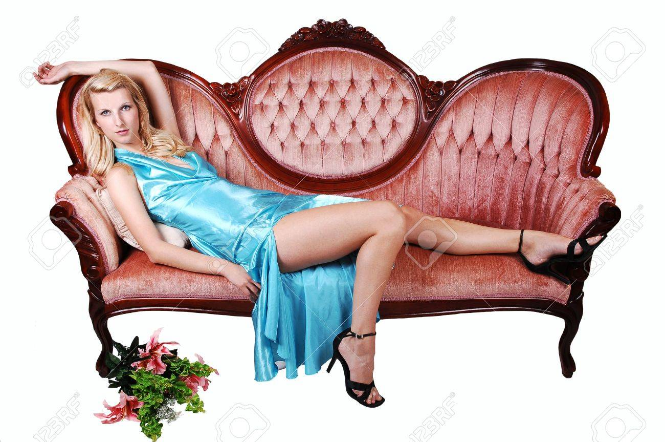 A young pretty woman with long blond hair and a light blue dress, lying on a pink sofa, shooing her nice long legs in high heels on white background. Stock Photo - 7282786