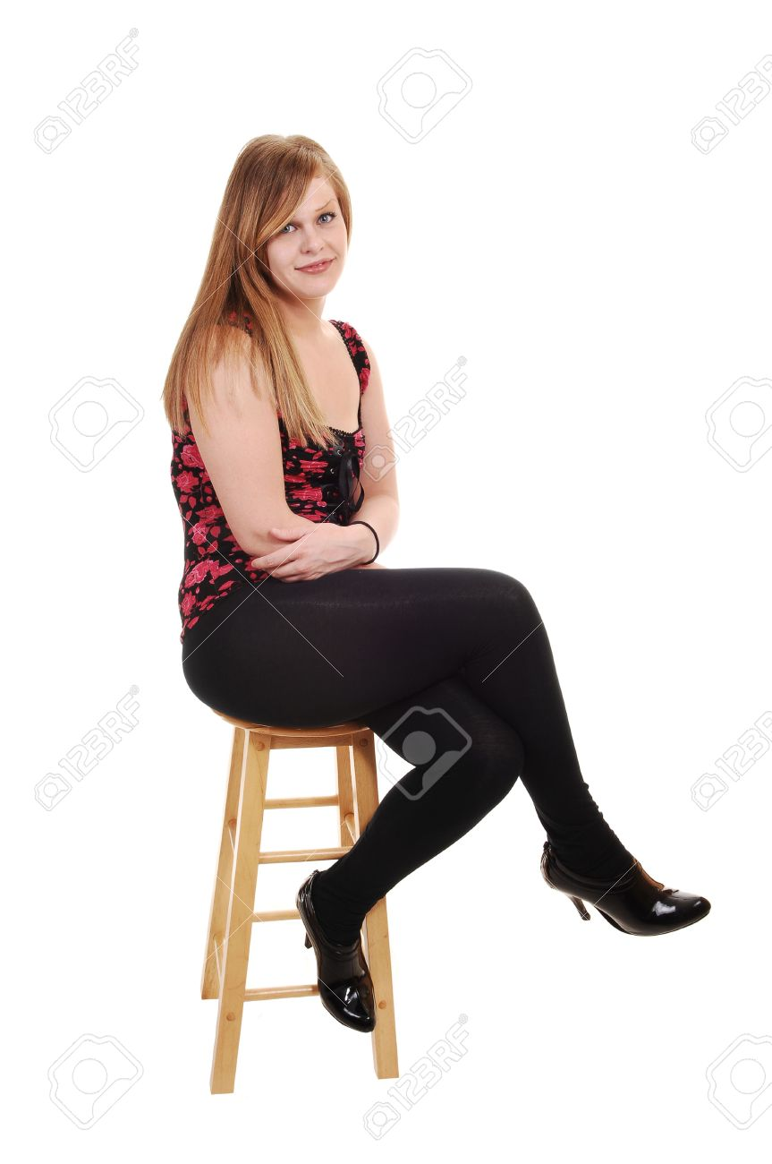 73d74b747 An pretty blond woman in black tights and a red black vest and high heels  sitting