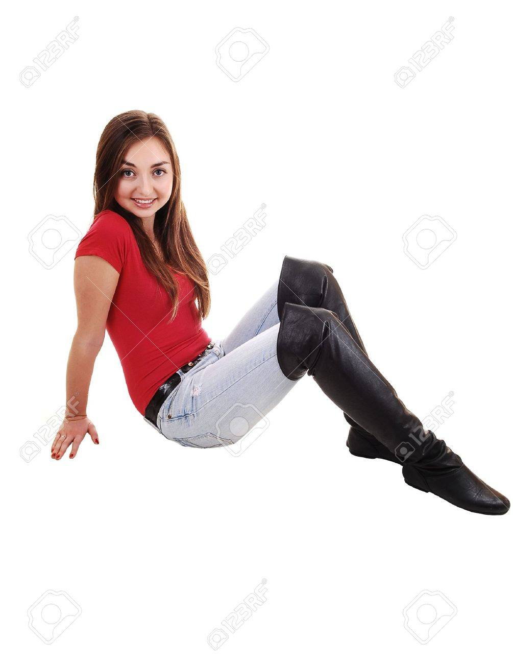 3971766009f A beautiful young girl sitting on the floor in long boots and jeans and a  red