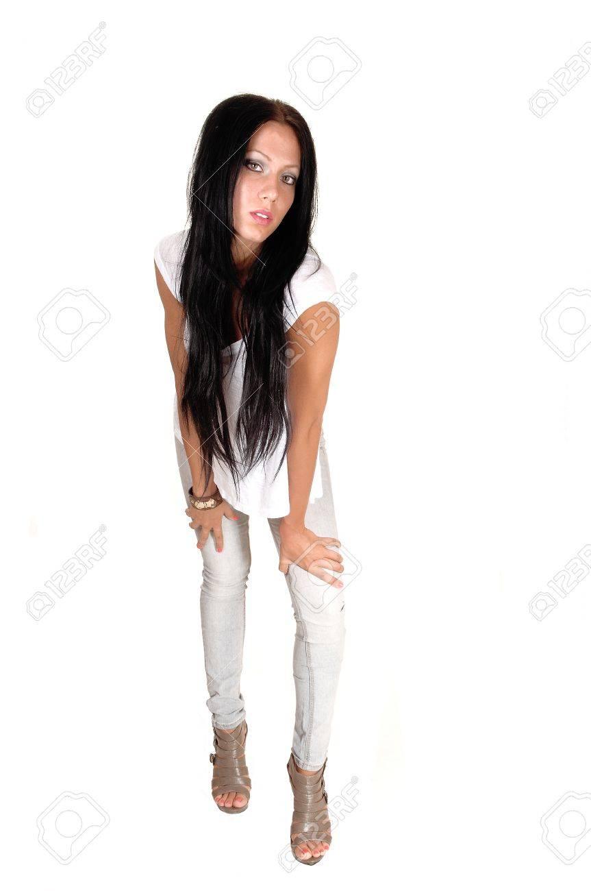 Une belle jeune femme aux longs cheveux noirs en jeans gris et talons hauts, debout à l'avant dans le studio pour fond blanc.