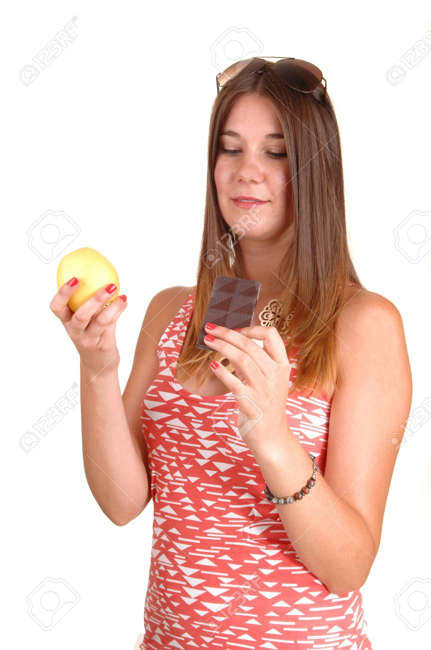 A young woman in a pink dress and sunglasses on her head can notdecide to eat an apple or chocolate, in white background. Stock Photo - 10536143