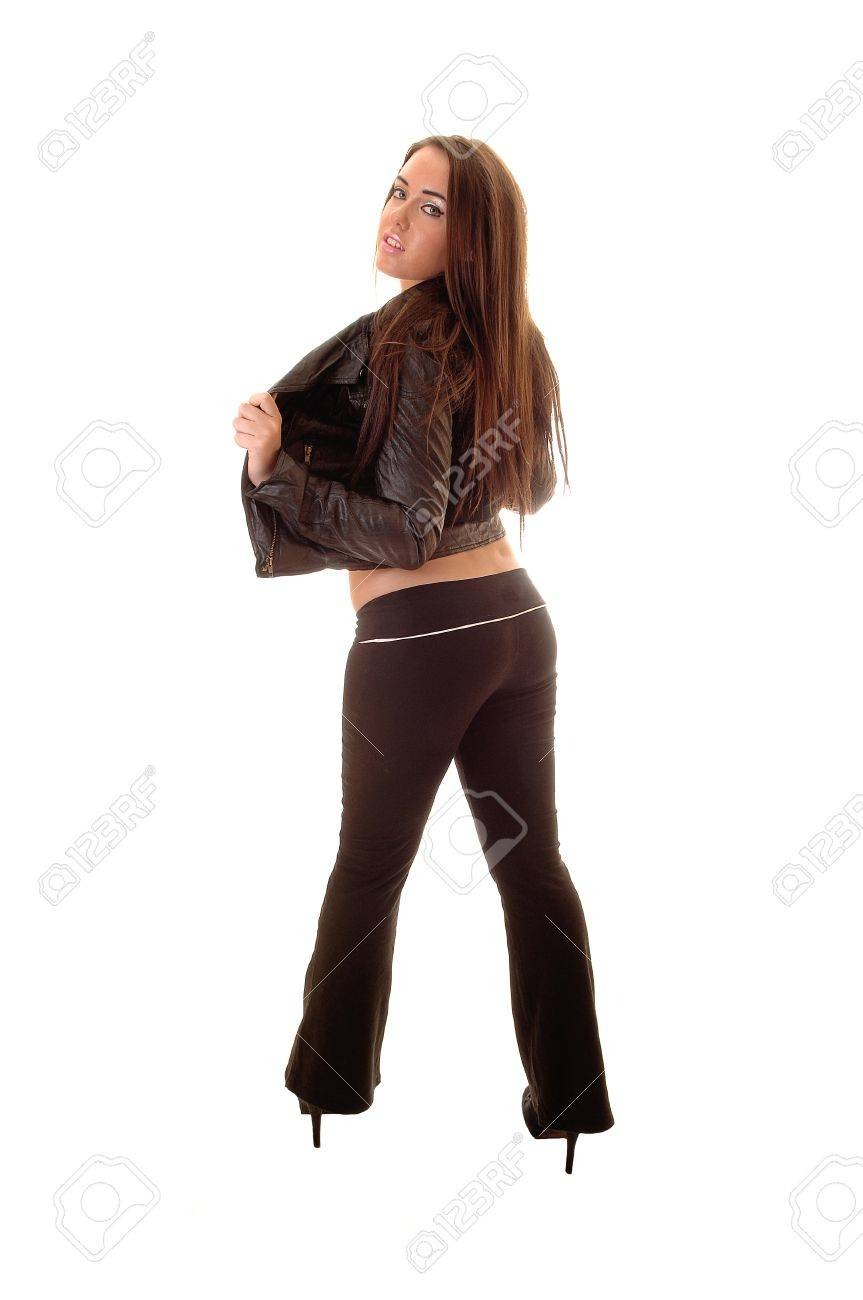 A young woman in black pants and leather jacket standing from the back,showing her nice figure and bum, on white background. Stock Photo - 10655062