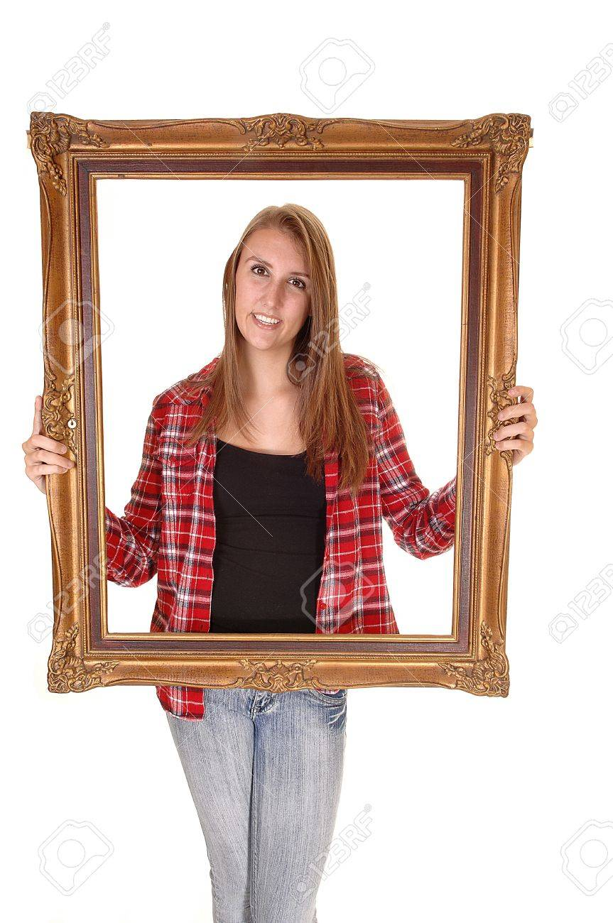 A tall pretty woman holding a picture frame for her upperbody, in jeans and a checkered shirt, over white. Stock Photo - 10828154