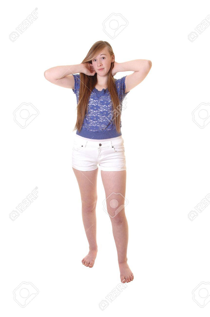 Une jeune adolescente en short blanc et chemisier bleu debout feetin à nu le studio, jouant avec ses cheveux brune longue pour fond blanc.
