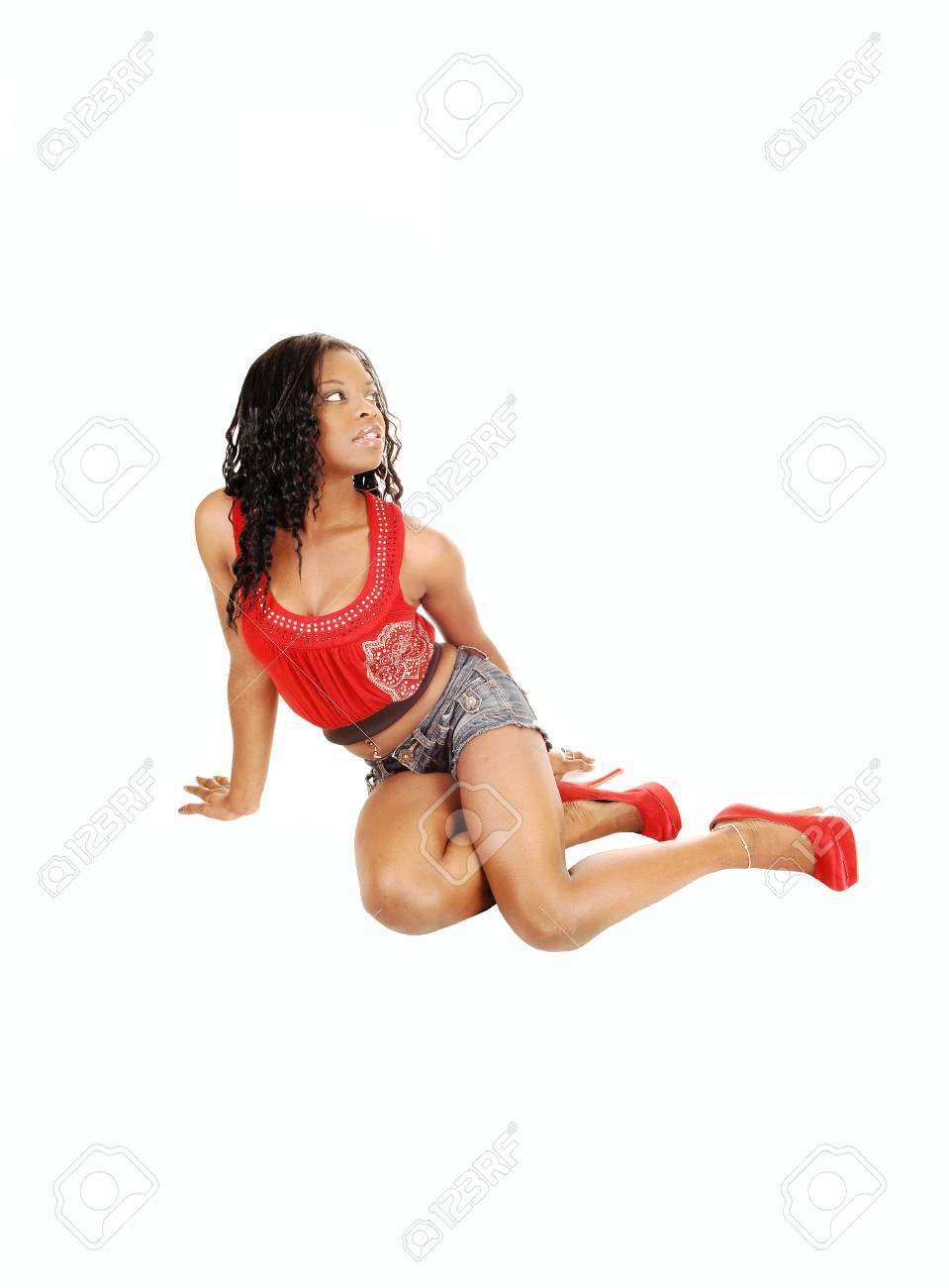 Une belle femme noire assise sur le sol en short en jean et un débardeur rouge, levant les yeux pour fond blanc