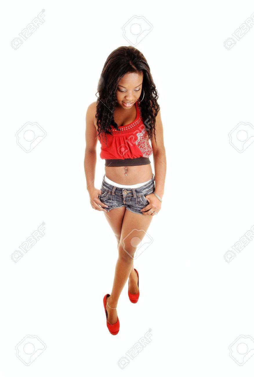 Une jolie femme noire en short en jean et un débardeur rouge et talons, standingfor fond blanc, regardant vers le bas
