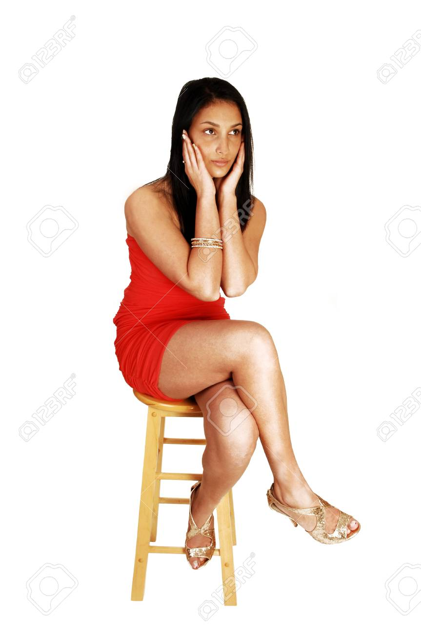 A young teen girl with a serious expression, in a red strapless dress sittingon a chair for white background, with gold colored high heels on Stock Photo - 17602552